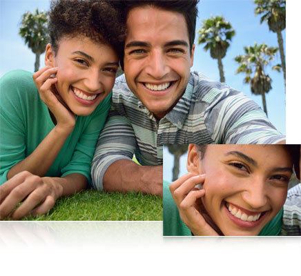 Nikon D5300 photo of a couple lying on the grass, looking at the camera and a closeup inset of the woman's face